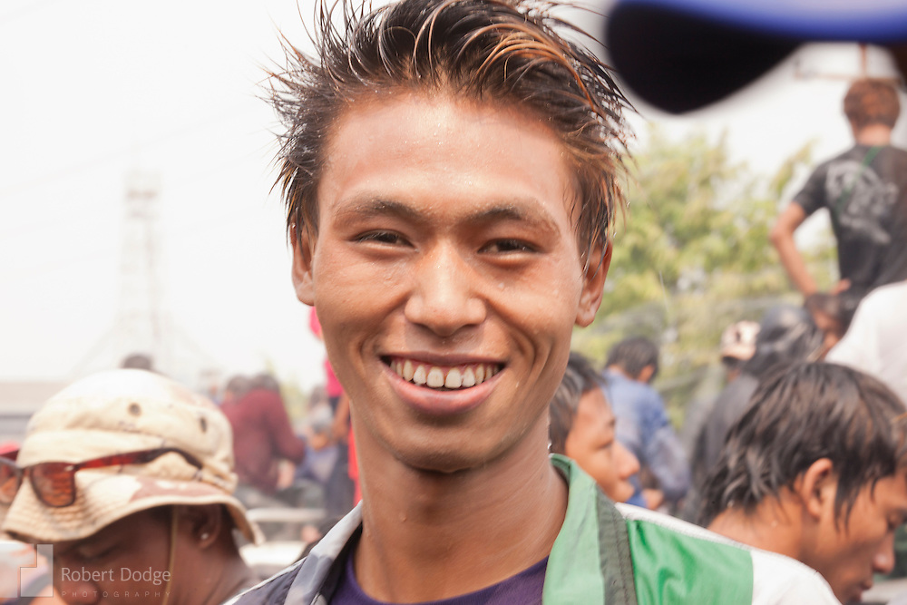 Mandalay, Myanmar- April 14, 2013: A young many poses for a photo during Myanmar's Thingyan Water Festival. Thingyan is held in April, one of the hottest months of the year in Myanmar. The water festival marks the country's New Year celebration and the festival includes lots of drinking, singing, dancing and theater. Wherever you are you are likely to get doused with water as the Burmese see this as a cleansing of the previous year's sins and bad luck and a blessing for good luck and prosperity in the year ahead. In the major cities of Mandalay and Yangon, large platforms are erected along major roadways and are equipped with high powered water hoses. The platforms, sponsored by large corporate donors, also have dance stages and play the latest pop and hip hop music. Thousands of residents pour into the streets by foot, motorbike and flatbed truck to get hosed under the platforms while they drink and dance. Many of the young celebrants wear their best clubbing clothes. And many of the party goers are men, having left their wives and girlfriends at home.