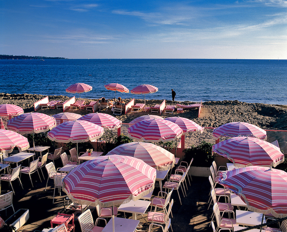 Pink stripped umbrellas cover the beach in Cannes on the Riviera, France.