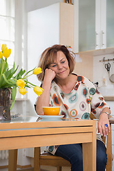 Senior woman in deep thought while having tea in the kitchen, Munich, Bavaria, Germany
