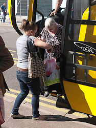 Carer helping old lady off a coach