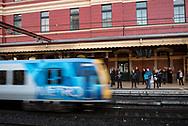 Melbourne, Australia - August 24, 2017: People wait on a train station platform at Flinders Street Station, the central transportation hub in Melbourne, for an arriving train.