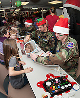 Macy Swormstadt gets her face painted by Brendan Drew from the Civil Air Patrol during the annual Christmas Village Thursday evening.  (Karen Bobotas/for the Laconia Daily Sun)