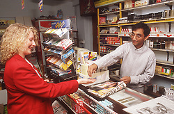 Newsagent working behind counter in news agency serving customer,