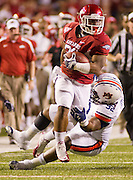 Arkansas running back Dennis Johnson (33) carries the ball past Auburn defensive tackle Kenneth Carter (92) during an NCAA college football game on Saturday, Oct. 8, 2011, in Fayetteville, Ark. (AP Photo/Beth Hall)