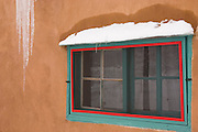 Bright window on adobe house with icicles