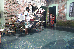 August 8, 2017 - Dhaka, Bangladesh - Bangladeshi people stands on water logged yard of their home at Demra, in Dhaka, Bangladesh. Mixing of rain water and toxic waste from industries has turned water into green. (Credit Image: © Suvra Kanti Das via ZUMA Wire)