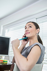 Businesswoman working on computer and talking on mobile phone, Munich, Bavaria, Germany