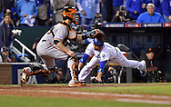 Oct 28, 2014; Kansas City, MO, USA; Kansas City Royals second baseman Omar Infante (right) scores a run past San Francisco Giants catcher Buster Posey in the fifth inning during game six of the 2014 World Series at Kauffman Stadium. Mandatory Credit: Peter G. Aiken-USA TODAY Sports
