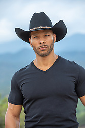 portrait of a hot black cowboy with green eyes