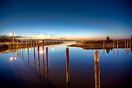 Perfectly still water creates detailed reflections on a March night at Rock Harbor.