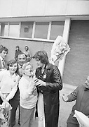 Johnny Logan on his return at Dublin Airport from Holland where he won the Eurovision Song Contest for Ireland with his entry What's Another Year..1980-04-21.21st April 1980.21-04-1980.04-21-80..Photographed at Dublin Airport..Johnny Logan looks at the bubbly as fans greet him.