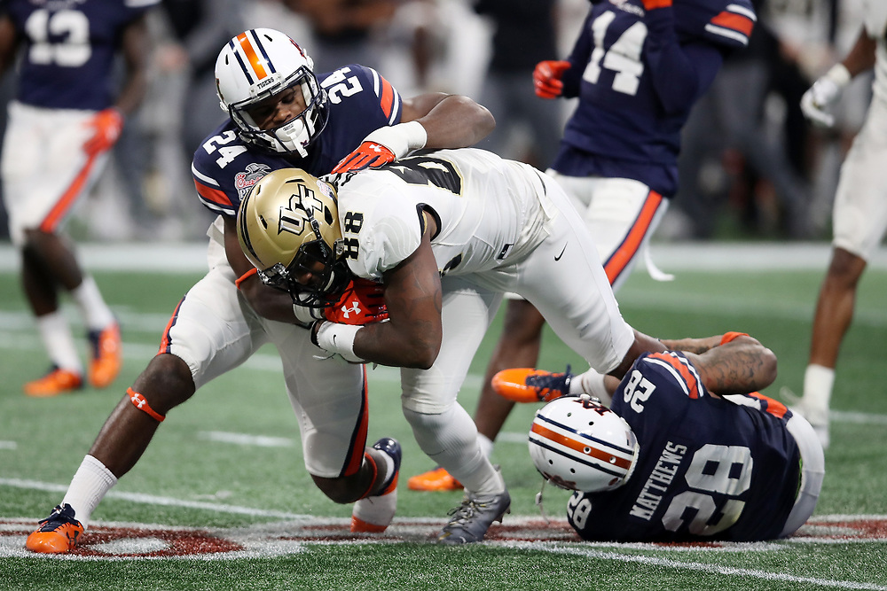 UCF Knights tight end Jordan Akins (88) is tackled by Auburn Tigers defensive back Daniel Thomas (24) and defensive back Tray Matthews (28) during the 2018 Chick-fil-A Peach Bowl NCAA football game on Monday, January 1, 2018 in Atlanta. (Jason Parkhurst / Abell Images for the Chick-fil-A Peach Bowl)