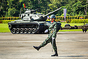 29 SEPTEMBER 2014 - NAKHON NAYOK, NAKHON NAYOK, THAILAND: A Thai non-commissioned officer marches past a parked tank at the retirement ceremony for more than 200 Thai generals including Gen. Prayuth Chan-ocha, who led the 22 May coup against the civilian government earlier this year. Prayuth has been chief of the Thai army since 2010. After his retirement, Gen. Prayuth will retain his posts as head of the junta's National Council for Peace and Order (NCPO) and Prime Minister of Thailand. Under Thai law, military officers must retire at 60 years of age. The 200 generals who retired with Prayuth were also his classmates at the Chulalomklao Royal Military Academy in Nakhon Nayok.    PHOTO BY JACK KURTZ