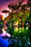 """""""Riflessioni di tramonto di Villa Borghese - Roma""""Sunset reflections of Villa Borghese – Rome""""…<br /> <br /> Villa Borghese in Roma is a famous Gardens and Museum begun in the early 17th century, highlighted by a """"Temple of Aesculapius"""" at the garden lake. The Temple is located in the gardens of Borghese in Roma and was styled in the ionic characteristic by Antonio Asprucci. The temple was perhaps built-in memory of the destroyed ancient temple to the god of Medicine on Tiber Island. The temple houses a statue of Aesculapius believed to be originally from the Mausoleum of Augustus.  Neglected over the centuries, it was restored by Vincenzo Pacetti and sold to Marcantonio Borghese IV in 1785. Stretching from above Piazza del Popolo to the top of Via Veneto, Villa Borghese crowns Rome in a glorious canopy of Green. Despite the onward march of the years and extensive developmental changes to Rome, Villa Borghese has remained a perennial and pleasant space, diluting the impact of an otherwise ever-expanding urban Metropolis. The Park was originally a private vineyard, redesigned and enlarged in 1605 to grandiose proportions for Pope Paul V's nephew, the Cardinal Scipione Borghese. However, it was named after the Borghese family on the condition that it boasted the most luxurious and magnificent dwelling in Rome. Visiting the very spaciously plush park and lovely atmosphere of tall secluding lavish trees, blissful gardens, and colorful reflective lakes, one is taken away from the city life and transported to a serene country paradise. Peace and relaxation encompass the body and soul and gives time and rumination of the historical and religious world capital which is the ever Eternal City of Roma."""
