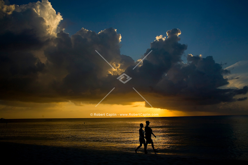 Jeannelle Fuentes Mora, left, and Andrew Gresham (holding 6-week-old baby Isabelle) enjoy a walk along 7-mile beach during the sunset in the Cayman Islands, British West Indies. Both reside in the Cayman Islands. Oct. 10, 2006. Photo by Robert Caplin ..Contact for Andrew is: Andrew.Gresham@gs.com