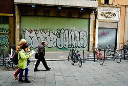 People walking past graphiti on a closed shop in the Via degli Orefici, Bologna, Italy<br /> <br /> (c) Andrew Wilson | Edinburgh Elite media