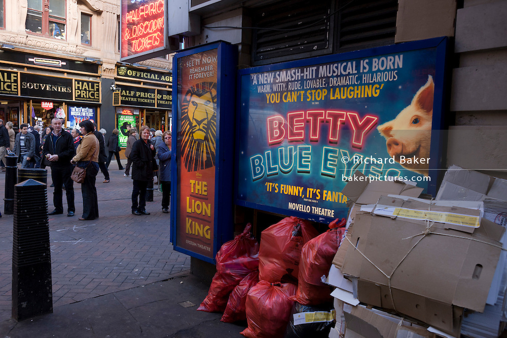 Piles of rubbish is stacked beneath a threatre poster for a west end production, near a theatre box office.