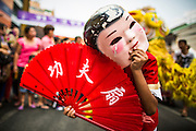 """10 FEBRUARY 2013 - BANGKOK, THAILAND:  A """"Laughing Buddha"""" accompanies a parade of Lion Dancers on Chinese New Year in Bangkok. The Buddhas are comic and acrobatic characters who interact with the crowd and tease the lion with a fan or a ball. The lion in turn will play with, chase, or even bite and kick the buddha depending on its mood. Because it is difficult for the lion dancers to see, the Buddhas also help the lions find their """"food"""", etc. Bangkok has a large Chinese emigrant population, most of whom settled in Thailand in the 18th and 19th centuries. Chinese, or Lunar, New Year is celebrated with fireworks and parades in Chinese communities throughout Thailand. The coming year will be the """"Year of the Snake"""" in the Chinese zodiac.   PHOTO BY JACK KURTZ"""