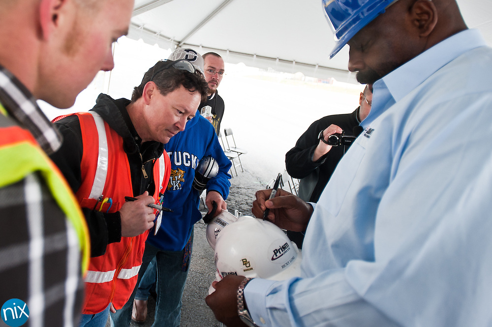 """Former Dallas Cowboy Ed """"Too Tall"""" Jones signs autographs for consruction workers during a topping out ceremony for the steel frame that will support a high-definition video board at Charlotte Motor Speedway Thursday morning. The 200-foot wide, 80-foot tall video board will debut during the track's race events in May.  (Photo by James Nix)"""
