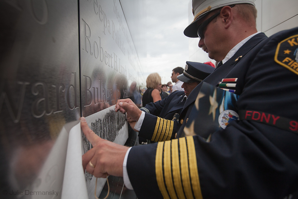 Steve Dyi and Joe Mastabdrea make a rubbing of  a colleagues name at  the Empty Sky Memorial 9/11 Memorial at Liberty State Park in New Jersey during the opening on September 10, 2011.<br /> The memorial is two 30-Ft rectangular towers  208 feet by 10 inches long,  the width of the World Trade Center towers and with the names of the 746 New Jerseyans who perished after the terrorist attacks on 9/11, 2001  etched in stainless steel.