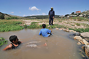 Israel, Negev, Two Beduin boys play in a water puddle