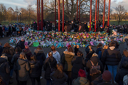 © Licensed to London News Pictures.13/03/2021. London,UK. Members of the public place floral tributes for Sarah Everard at the band stand in Clapham Common, south London after the Reclaim These Streets vigil this evening was officially cancelled. Serving police constable Wayne Couzens, 48, appeared at Westminster Magistrates Court today and has been charged with with the kidnap and murder of Sarah Everard. Photo credit: Marcin Nowak/LNP