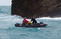 Nick Sharpe (red) in the small boat helps Nick Hancock (yellow) as he  swims away from Rockall, after his reconnaissance mission for a future 60 day occupation of Rockall. The Rockall Jubilee Expedition, a unique endurance expedition to be undertaken by Nick, in order to raise funds for Help for Heroes .©Michael Schofield..