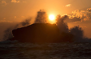 Dawn waves break over a large rock in Old Town Bay, St Mary's. Isles of Scilly