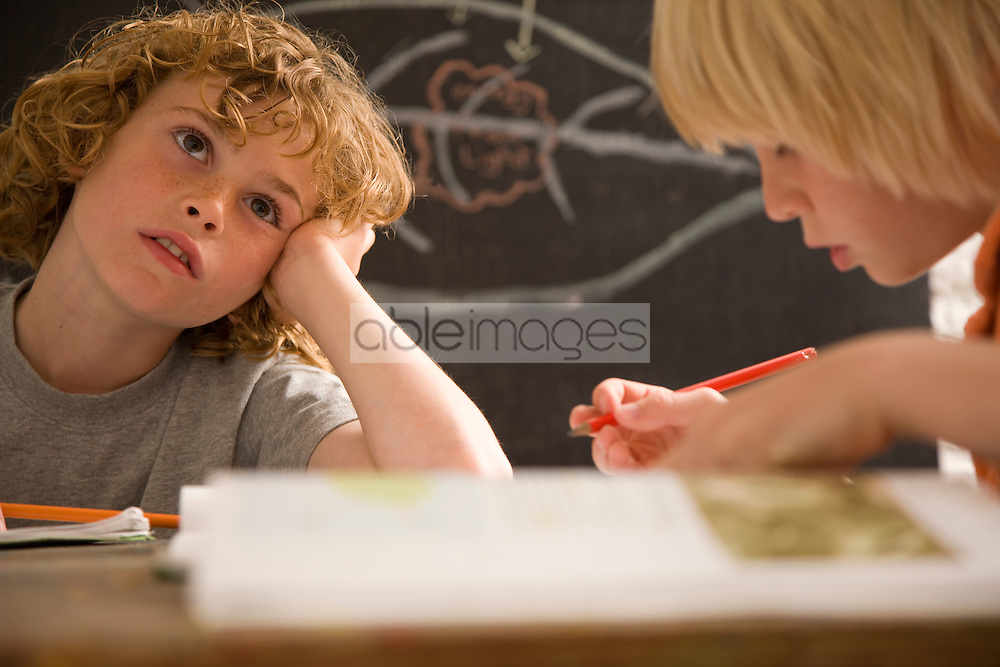 Two young boys writing and sitting at desk in the classroom one of them is day dreaming