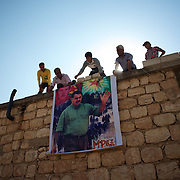 August 12, 2012 - Kafa Safra, Efrin, Syria: Syrian Kurdish men hang a banner with a picture of the Kurdistan Workers' Party (PKK) leader, Abdullah Öcalan, during the funeral of PKK fighter taking place near the village of Kafra Safra. Around five thousand Syrian Kurdish attended the funeral and ceremony of martyrdom of Taliz Gadalum, killed days earlier during combat against the Turkish army...PKK has been fighting an armed struggle against the Turkish state for an autonomous Kurdistan and greater cultural and political rights for the Kurds in Turkey, Iraq, Syria and Iran. Founded on 27 November 1978 in the village of Fis, was led by Abdullah Öcalan. The PKK's ideology was originally a fusion of revolutionary socialism and Kurdish nationalism - although since his imprisonment, Öcalan has abandoned orthodox Marxism. The PKK is listed as a terrorist organization by Turkey, the United States, the European Union and NATO. (Paulo Nunes dos Santos)