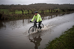 © Licensed to London News Pictures. 03/02/2021. Old Windsor, UK. A man cycles his bike through flood water which has closed the Windsor Road between Windsor and Staines, where the River Thames has broken it's banks. Large parts of the UK experience more wet conditions which is expected to bring further flooding. Photo credit: Ben Cawthra/LNP