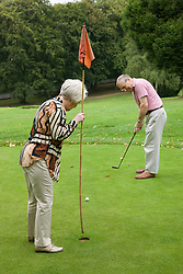Older couple playing pitch and putt at the Park,