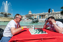 © Licensed to London News Pictures. 18/07/2021. LONDON, UK. Two grandmasters have a warm up game at Chess Fest in Trafalgar Square.  The event celebrates the game of chess and visitors can learn the game, play chess or challenge a Grandmaster.  Also, to celebrate the 150th anniversary of Lewis Carroll's Alice Through the Looking Glass book which featured the game of the chess, 32 actors dressed as Alice Through the Looking Glass characters stand on a giant chessboard replaying a game based on the book.  Photo credit: Stephen Chung/LNP