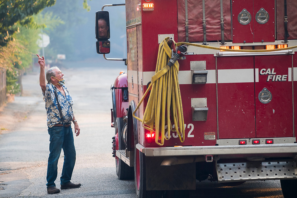 Boulder Creek resident Mike Smith talks with a Cal Fire firefighter on Ridge Road near Boulder Creek, Calif. on Aug. 21, 2020 as the CZU Lightning Complex Fire burns near by.