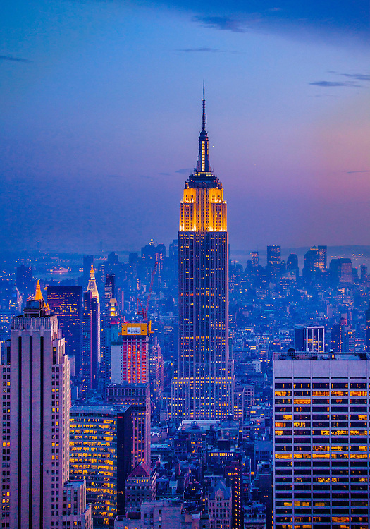 A deep blue and magenta, New York skyline at dusk, seen from the Top of the Rock observation deck in Rockefeller Center's RCA (now Comcast) Building, aka 30 Rock, looking south to Midtown, the Empire State Building and Lower Manhattan.