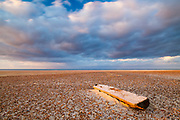 Warm evening light bathes this low tide scene at Holkham Bay in North Norfolk. Driftwood lies amongst the sand and shingle with the North Sea beyond. October in East Anglia, England, UK.