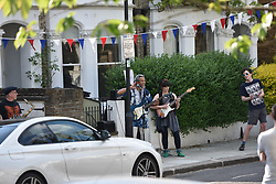 © Licensed to London News Pictures. 08/05/2020. London, UK. Residents in west London enjoy the bank holiday weather while observing social distancing on VE Day (the 75th anniversary of Victory in Europe) under lockdown. Hanging bunting, playing music and speaking to neighbours households mingle at arms length. Photo credit: Guilhem Baker/LNP