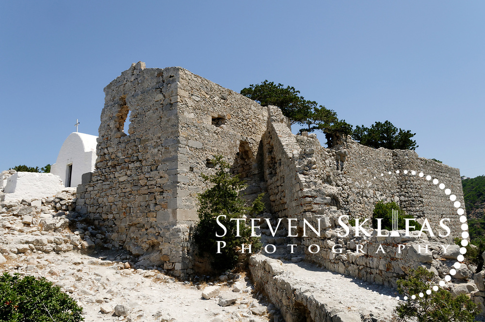 Rhodes. Greece. Monolithos, a ruined medieval crusader castle perched atop the enormous crag called Monopetra on the west coast of Rhodes Island. Built by the Knights of St John in 1476, the once impregnable fortress offers great views of the wild island landscape and wild coastline and the castle is easily reached by tourists. The island of Rhodes is the largest of the Dodecanese Island group and one of the most popular Greek Islands.