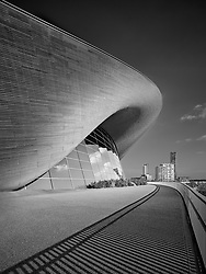 It was a long time before I finally got around to photographing the architecture of the 2012 Olympics site in London. I admired Zaha Hadid for a long time and her Aquatic Centre is certainly better off in its legacy format without the temporary seating grandstands. I waited a long time so an hour more waiting for just the right light was little hardship.<br /> <br /> Monochrome Print of the Year - Bath Photographic Society 2020
