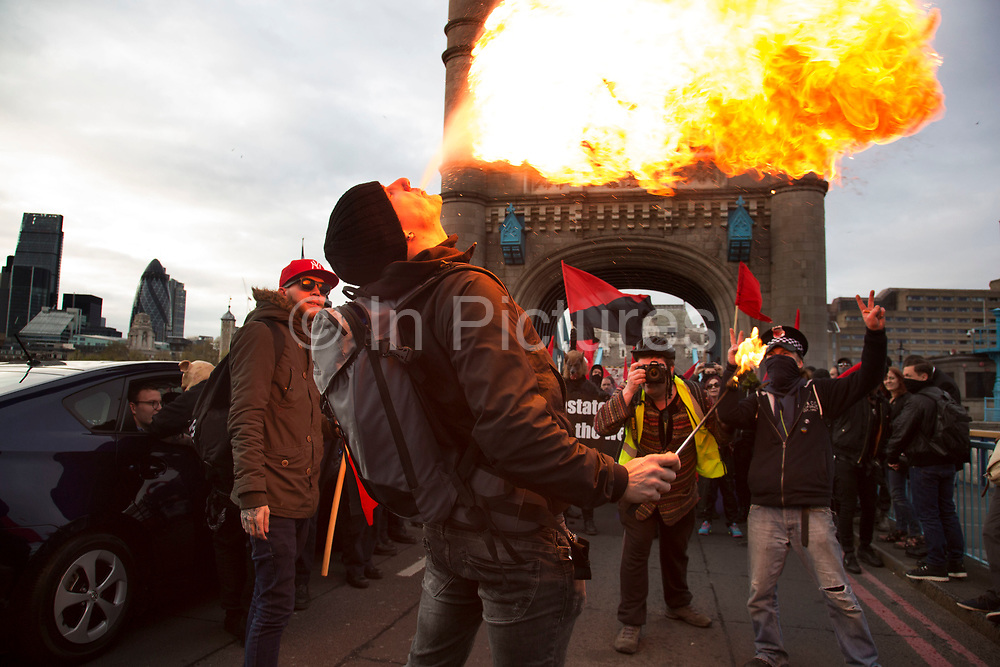 Anarchists gather as a black bloc for the Fuck Parade to party and protest at the class and wealth divide between rich and poor and the gentrification of London, the demonstration was organised by anarchist group Class War on May 1st 2016 in London, United Kingdom. The parade is now part of the May Day activism calendar as dissatisfaction about the establishment, the police and the inadequacy of the press is highlighted. A fire breather shoots up a flame at the protest gathers on Tower Bridge. (photo by Mike Kemp/In Pictures via Getty Images)