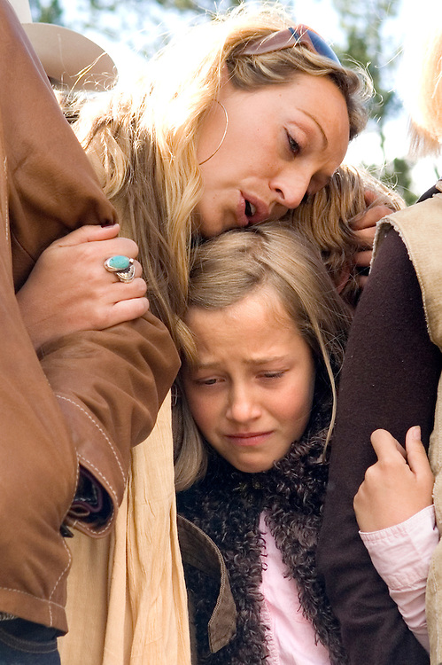 Cameron Garnick's daughters Jessica, top, and Cheyenne, bottom, console each other during their father's funeral on Tuesday at the Triangle C Ranch near Dubois. The family sang songs and told stories about a man who embodied the western spirit while remaining involved with art and theater throughout his life.