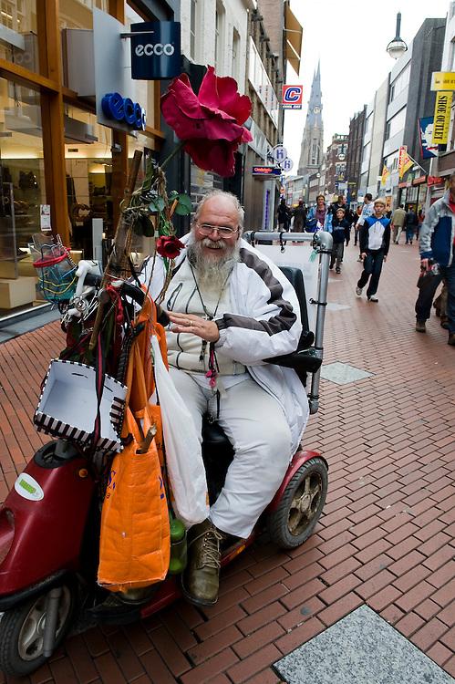 Nederland, Eindhoven, 23 okt 2009.Een man in een electrische rolstoel in een winkelstraat in Eindhoven probeert mensen in Jezus te laten geloven. Met een luidspreker roept hij zijn teksten rond en rijdt kriskras tussen de mensen in een drukke winkelstraat door. ..Foto (c) Michiel Wijnbergh.