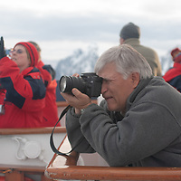 Tourists aboard the National Geographic Endeavor photograph mountains above the Lemaire Channel, Antarctica.