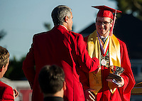 Taylor Gagne is congratulated by Steve Tucker LHS Academic Coordinator following his Valedictorian's Address during Laconia High School Commencement Friday evening.  (Karen Bobotas/for the Laconia Daily Sun)