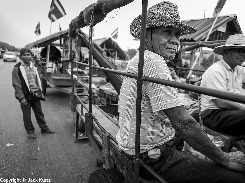 21 FEBRUARY 2014 - KHLONG CHIK, PHRA NAKHON SI AYUTTHAYA, THAILAND: A Thai farmer on the highway south of Ayutthaya. About 10,000 Thai rice farmers, traveling in nearly 1,000 tractors and farm vehicles, blocked Highway 32 near Bang Pa In in Phra Nakhon Si Ayutthaya province. The farmers were traveling to the airport in Bangkok to protest against the government because they haven't been paid for rice the government bought from them last year. The farmers turned around and went home after they met with government officials who promised to pay the farmers next week. This is the latest blow to the government of Yingluck Shinawatra which is confronting protests led by anti-government groups, legal challenges from the anti-corruption commission and expanding protests from farmers who haven't been paid for rice the government bought.    PHOTO BY JACK KURTZ