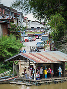16 JUNE 2015 - SUNGAI KOLOK, THAILAND:  People wait on the Malaysian side of the border to come to Thailand. The border between Thailand and Malaysia in Sungai Kolok, Narathiwat, Thailand. Thai and Malaysians cross the border freely for shopping and family visits. The border here is the Kolok River (Sungai is the Malay word for river).        PHOTO BY JACK KURTZ