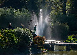 © Licensed to London News Pictures. 27/10/2014. Cliveden, UK. A boy survey the water garden.  People walk through the autumnal trees in the morning sunshine at Cliveden House in  Buckinghamshire. Today 27th October 2014. Photo credit : Stephen Simpson/LNP