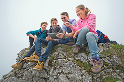 Father teenage kids sitting on rocks using iPad