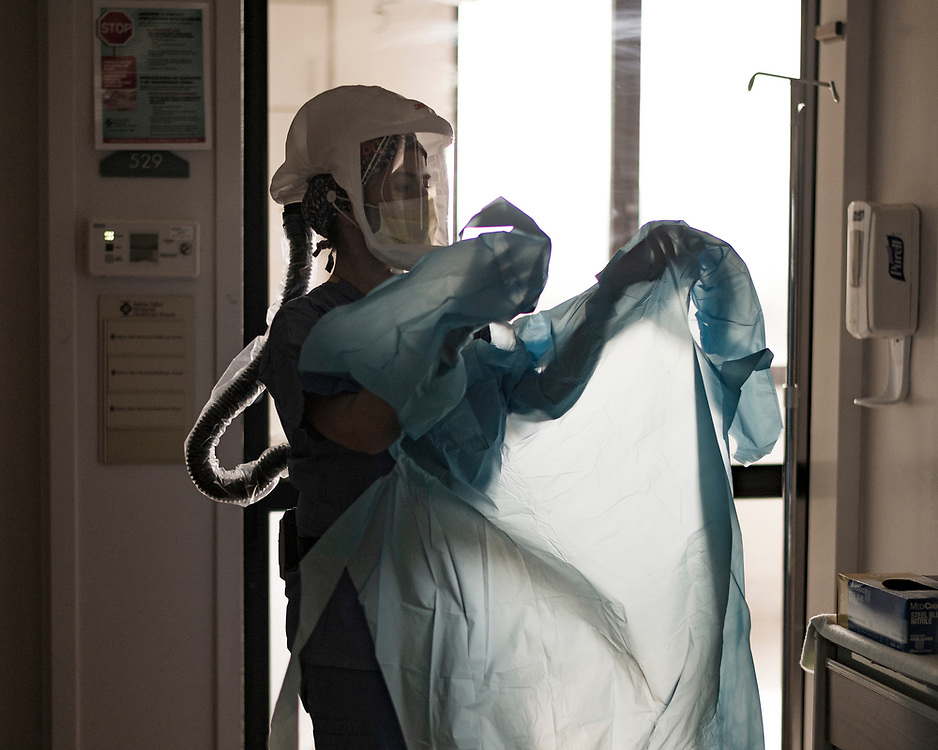 Nurse Dalila Ceja adjusts her gown before entering a patient's room in the in the COVID-19 Intensive Care Unit at Salinas Valley Memorial Hospital in Salinas, Calif. on Feb. 23, 2021.