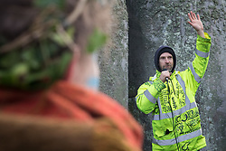 An activist addresses over one hundred people, including local residents, climate and land justice activists and pagans, at a Mass Trespass at Stonehenge on 5th December 2020 in Salisbury, United Kingdom. The trespass was organised in protest against the approval by Transport Secretary Grant Shapps of a £1.7bn project for a two-mile tunnel beneath the World Heritage Site and a further eight miles of dual carriageway for the A303, as well as the government's £27bn Road Investment Strategy 2 (RIS2).